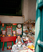 CHINA, Macau, Old Chinese woman dining at table in messy house