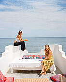 MEXICO, Sayulita, two young women relaxing on terrace with sea in background, portrait