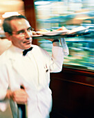 MEXICO, Mexico City, waiter carrying tray of food and bottle at Danubio Restaurant.