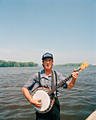USA, Minessota, Lacrosse, portrait of mature man playing banjo against the Mississippi River.