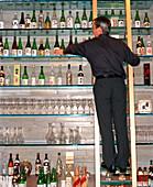 USA, Nevada, Las Vegas, bartender arranging bottle of wine at Okada Restaurant.