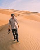 OMAN, Muscat, mature man walking in desert, holding camera