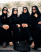 OMAN, Muslim women sitting side by side in traditional clothing at the Barr Al Jissa Resort and Spa