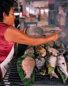 PERU, Amazon Rainforest, South America, Latin America, vendor grilling fishes on coal at the Bellavista Market.