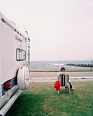 USA, Rhode island, Newport, relaxed mid adult man sitting in beach chair next to his motorhome.