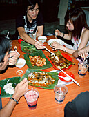 SINGAPORE, Asia, group of people eating dinner at Chinatown restaurant