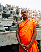 SRI LANKA, Asia, portrait of a monk with Buddha statues in the background