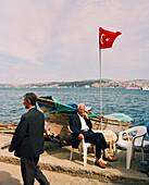TURKEY, Istanbul, portrait of a fisherman sitting with Turkish flag beside it