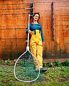 USA, Alaska, young woman holding fishing net, Redoubt Bay Lodge
