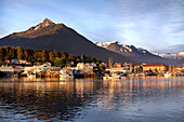 ALASKA, Sitka, a peaceful view of homes and fishing boats along the shore in Sitka Harbor at sunset, Crescent Bay