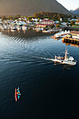 ALASKA, Sitka, kayakers take a rest in Sitka Harbor while a fishing boat passes by