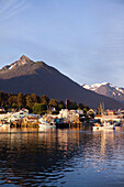 ALASKA, Sitka, a peaceful view of homes and fishing boats along the shore in Sitka Harbor at sunset, Mount Verstovia peak in the distance