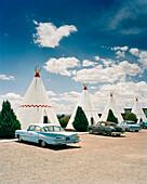 USA, Arizona, Holbrook, classic cars parked by teepees, Wigwam Motel