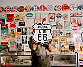 USA, Arizona, man holding sign Arizona US 66 in a sign store, Holbrook