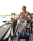 Aruba, Surfside Marina, a young woman sits drinking a glass of wine by the Caribbean Sea, Pinchos Bar & Grill