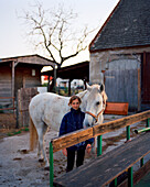 AUSTRIA, Podersdorf, a young girl Denise stands with her horse in front of her home, Burgenland