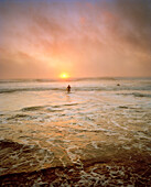 USA, California, surfer getting into the water at sunset, Ocean Beach, San Francisco