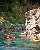 USA, California, people kayaking Salmon River and man diving off rocks, Forks of Salmon