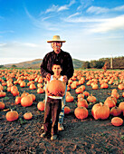 USA, California, senior man standing with his grandson in a pumpkin patch, Half Moon Bay