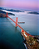 USA, San Francisco, an aerial view of a container ship passing under the Golden Gate Bridge, a view towards the Marin Headlands, Tiburon and Angel Island