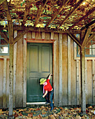 USA, California, girl closing a door in the Fall