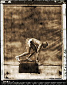 USA, California, track and field athlete in starting position, Los Angeles (B&W)