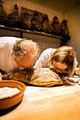 USA, California, chefs smelling cured meat in kitchen, Eccolo Restaurant, Berkeley