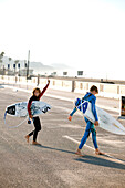 USA, California, Malibu, young surfer boys are excited to go surfing at Zuma Beach