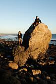 USA, California, Malibu, El Pescador Beach, Parker and his friend April explore the coastline at the end of the day