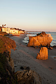 USA, California, Malibu, El Matador beach at sunset, large rock formations with Malibu beach homes in the distance
