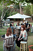 USA, California, Malibu, friends socialize and drink wine together