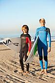 USA, California, Malibu, portrait of young male surfers at Zuma Beach