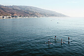 USA, California, Malibu, four paddleboarders pass by the Malibu pier on calm seas, looking South along the Malibu coast