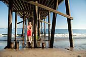 USA, California, Malibu, former Malibu mayor and the owner of Zuma Jay surf shop Jefferson Wagner stands with his surfboard under the Malibu Pier, Surfrider Beach