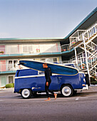 USA, California, Capitola, a surfer with a blue longboard walks in fronr of a blue VW bus on his way to go surfing