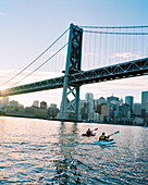 USA, California, San Francisco, a man and woman kayak in the San Francisco Bay under the Bay Bridge, the city of San Francisco in the distance