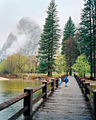 USA, California, Yosemite National Park, kids run across a bridge over the Merced River near Curry Village