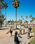 USA, California, Los Angeles, Venice Beach, surfers and bikers on the Venice Beach Boardwalk