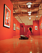 USA, California, Santa Monica, a young woman sits and admires artwork at an exhibit at the Santa Monica Public Library