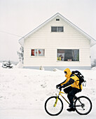 CANADA, man riding bicycle in snow in front of house, Fernie