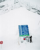 CANADA, person standing shoveling snow from around sign, Fernie Ski Area