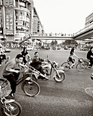 CHINA, Hangzhou, people riding bicycles and motorcycles in an urban area (B&W)