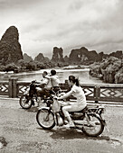 CHINA, Guilin, people traveling in motorcycles over bridge in rural Guilin (B&W)