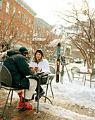 USA, Colorado, Aspen, couple wearing ski gear having coffee at an outdoor table in the winter, Downtown