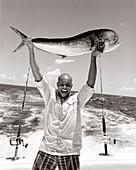 USA, Florida, man on boat holding up the catch of the day, Mahi Mahi, Islamorada (B&W)