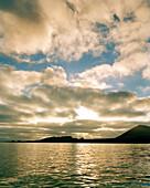 ECUADOR, Galapagos Islands, Floreana Island and seascape against cloudy sky at Sunset