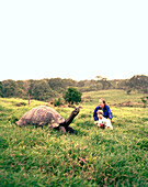 ECUADOR, Galapagos, Santa Cruz Island, mother and son observing a giant tortoise in the highlands