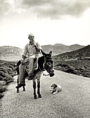 GREECE, Patmos Island, portrait of a shepard Stephanos riding his donkey Alekos from the sea to his animals inland (B&W)
