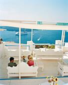 GREECE, Santorini, Fira, a young couple enjoys a drink and shade high above the Mediterranean Sea on the island of Santorini