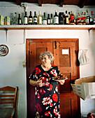 GREECE, Patmos, Diakofti, Dodecanese Island, Katerina Grillakis holds a plate of fried zucchini balls in the kitchen at her Diakofti Taverna